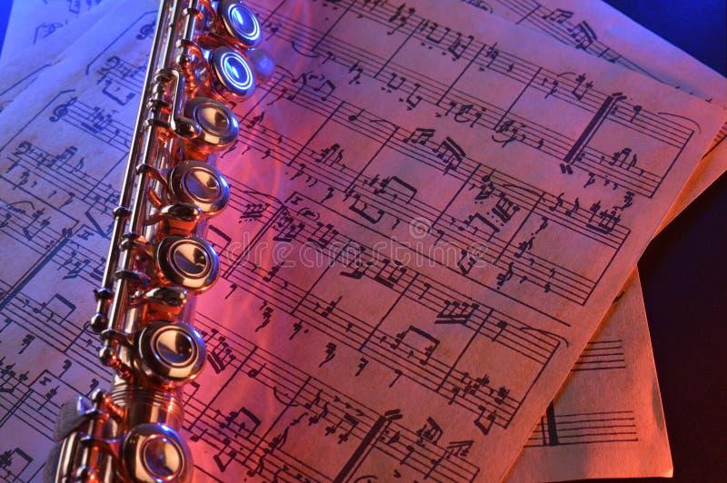 La flauta transversal y el azul rojo de la vieja partitura iluminaron el elevat imágenes de archivo libres de regalías