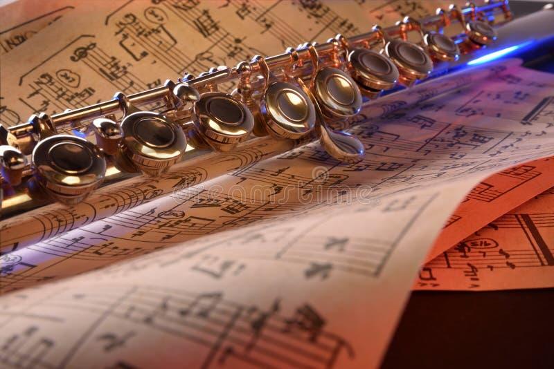 La flauta transversal y el azul rojo de la vieja partitura iluminaron el frente imagen de archivo