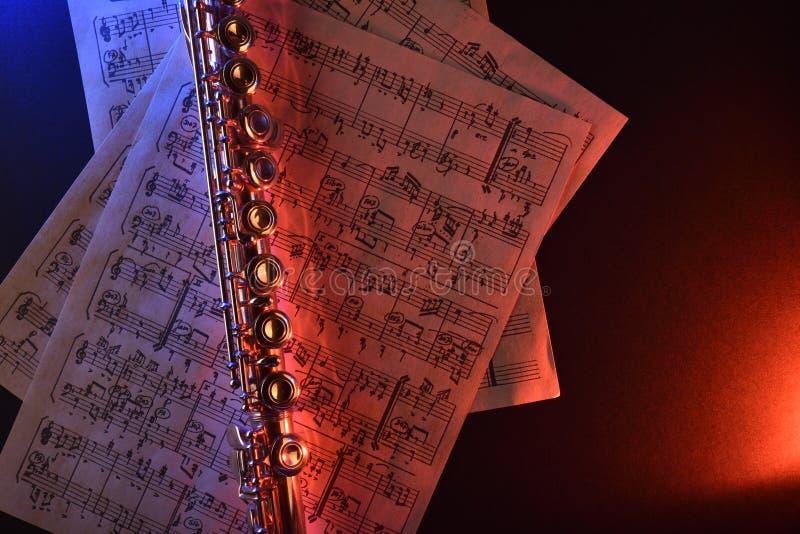 La flauta transversal y el azul rojo de la vieja partitura iluminaron el top fotos de archivo
