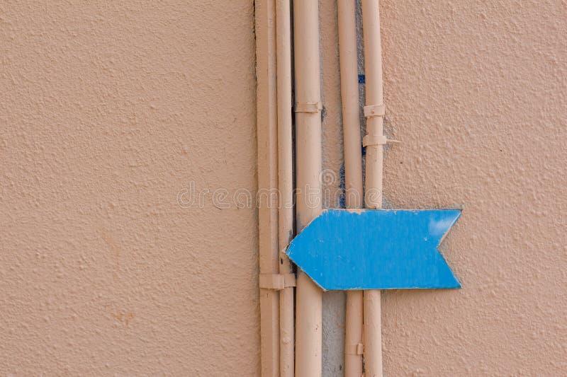 La flecha azul en la pared de un edificio fotos de archivo