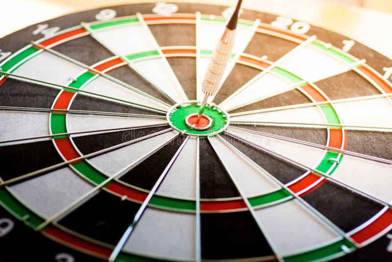 La flecha del dardo que golpea en el centro de la blanco de la diana usando como negocio de la blanco del fondo, alcanza y victor fotografía de archivo