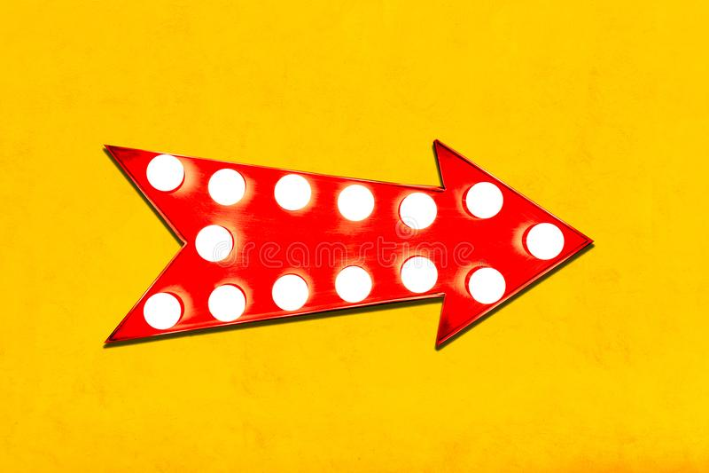 La flecha roja retra formó la señal de dirección metálica iluminada colorida de la exhibición del vintage con las bombillas que b imagen de archivo libre de regalías