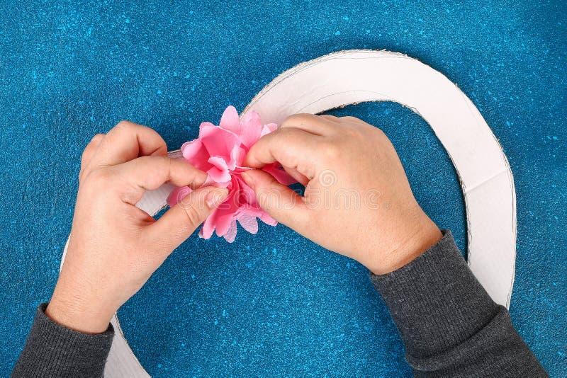 La fleur artificielle décorée par guirlande en forme de coeur a fait les serviettes roses de papier de soie de soie photo libre de droits