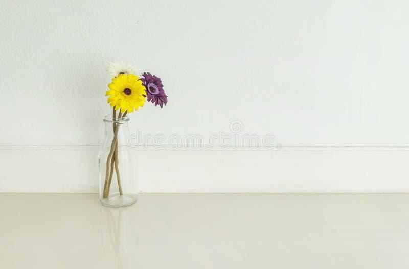 La fleur colorée artificielle de plan rapproché sur la bouteille en verre transparente sur le plancher de marbre brouillé et le m photos stock