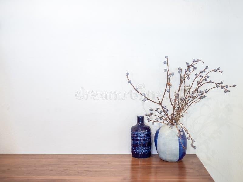 La fleur sèche par cru dans le vase en céramique décorent sur la table en bois sur le fond blanc de mur photo stock
