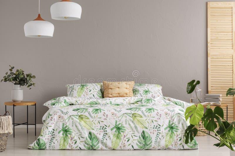 La fleur verte dans le vase sur le nightstand à côté du lit grand avec la literie et la pêche florales a coloré l'oreiller, l'esp image libre de droits