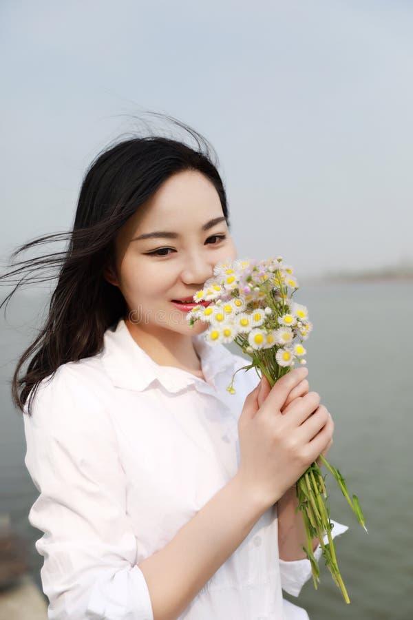 La flor causual descuidada libre del olor de la belleza por una playa del río del océano del lago goza relaja el tiempo al aire l imágenes de archivo libres de regalías