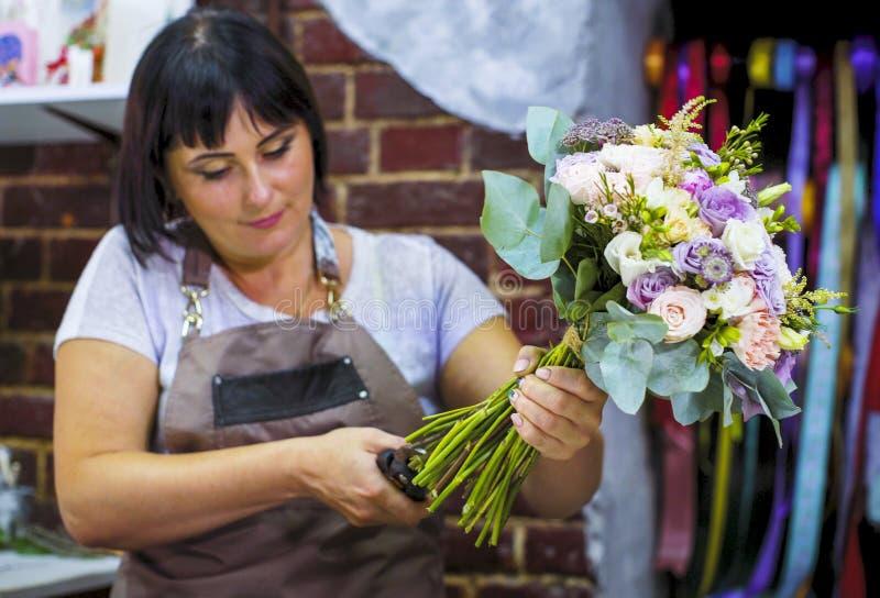 La flor de corte profesional del florista proviene con las tijeras en ramo de la boda en estudio del diseño floral foto de archivo