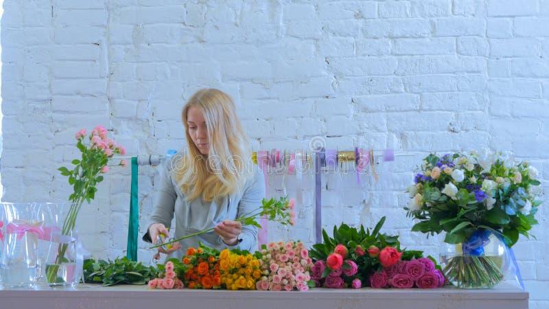 La flor de corte profesional del florista proviene en la tienda de flor fotografía de archivo libre de regalías