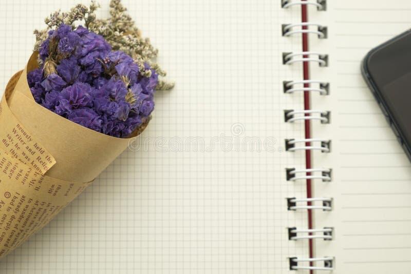 La flor del ramo y el teléfono elegante pusieron el papel vacío del cuaderno imagenes de archivo