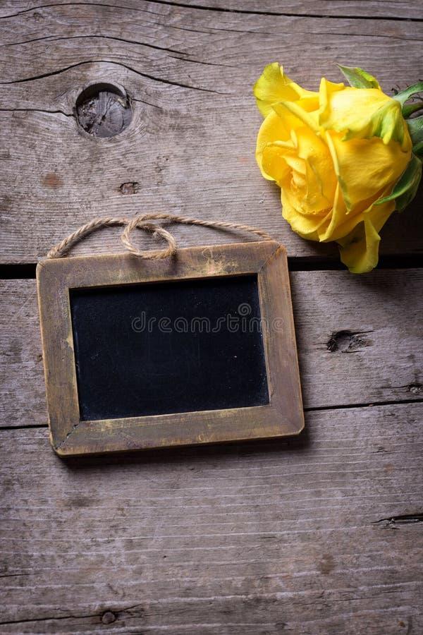La flor fresca de la rosa del amarillo y vacia la pequeña pizarra en rústico fotos de archivo