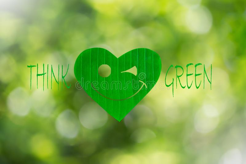 La foglia verde a forma di cuore sorridente con testo pensa il verde sul fondo vago del bokeh royalty illustrazione gratis