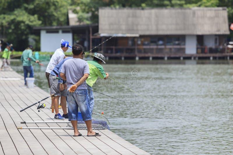 La folla del pescatore sta pescando in un lago fotografia stock