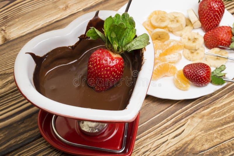 La 'fondue' de chocolate con las fresas y las frutas sirvió en un restaurante Día del `s de la tarjeta del día de San Valentín foto de archivo
