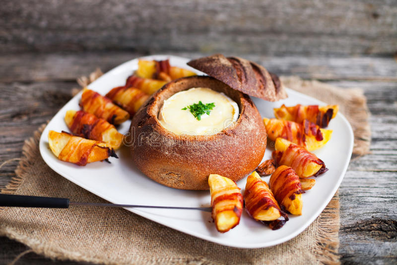 La fondue de fromage chaude savoureuse a servi dans un petit pain de pain avec des pommes de terre et photo stock