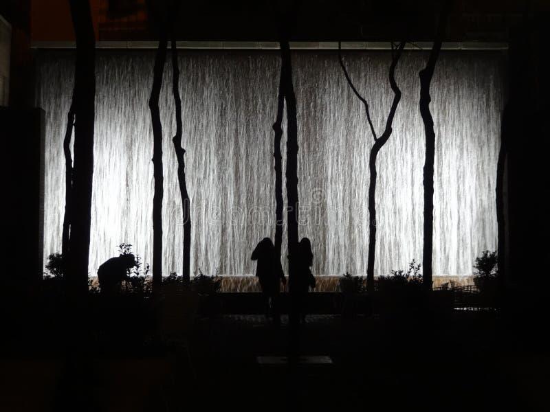 La fontaine de mur rougeoie la nuit avec des silhouettes à New York City image stock