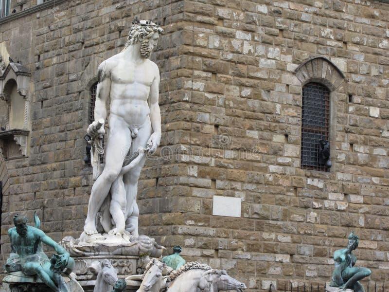 La fontana di Nettuno e il Palazzo Vecchio a Firenze, Italia Dettaglio della statua di Nettuno fotografie stock