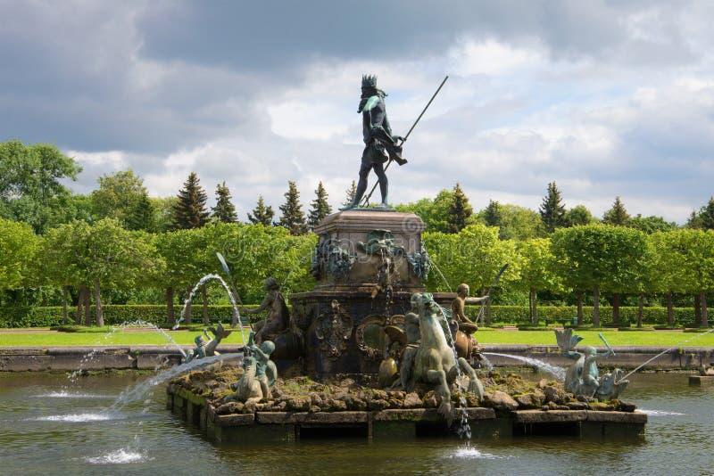 La fontana il Nettuno nel parco superiore di un complesso del palazzo nel pomeriggio nuvoloso di luglio Peterhof fotografia stock libera da diritti