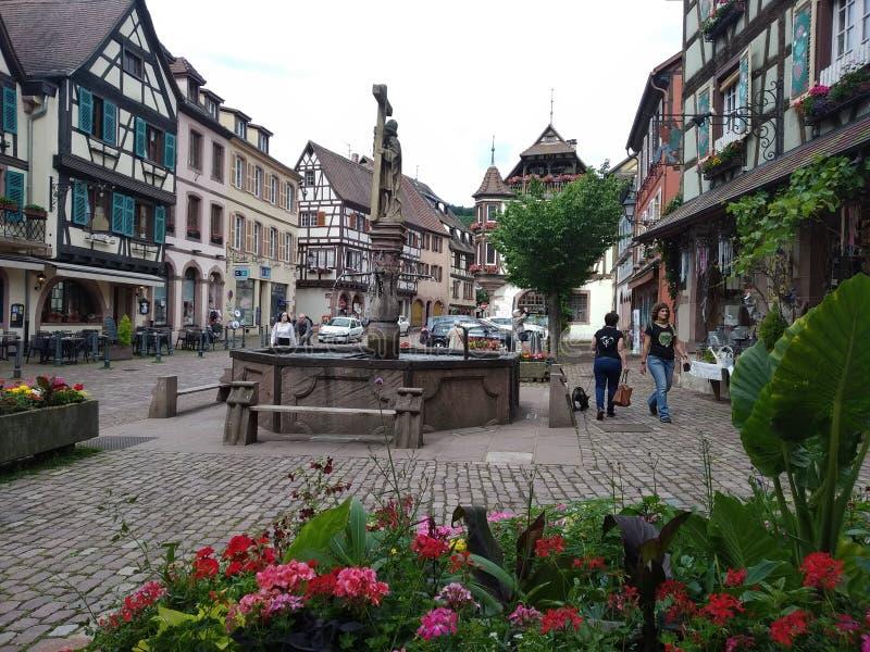 La fontana nel centro di Kaysersberg, circondato dalle case tipiche nello stile renano immagini stock libere da diritti