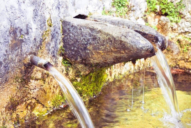 La fonte di pietra di acqua potabile viene da una montagna - immagine con lo spazio della copia fotografia stock libera da diritti
