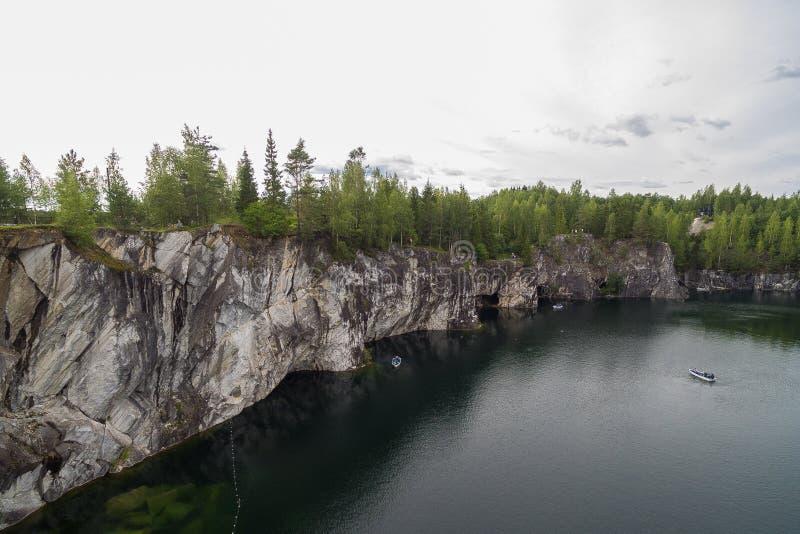 La forêt sur les pierres au-dessus du lac arrose image libre de droits