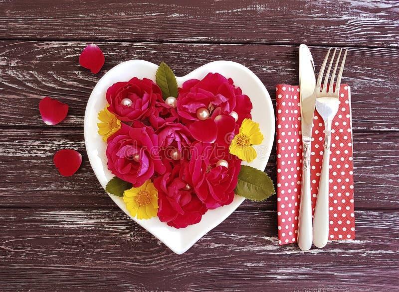 la forcella, coltello, cuore del piatto, fiore è aumentato su fondo di legno fotografia stock