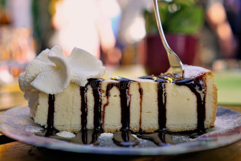La forcella ha conficcato la torta di formaggio gastronomica, salsa di cioccolato, panna montata - primo piano immagini stock