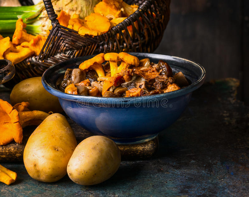 La foresta cucinata si espande rapidamente in ciotola e patata rustiche su fondo rustico scuro, vista frontale Cottura di autunno fotografia stock