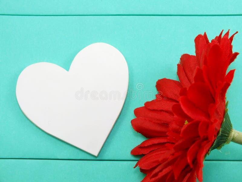 La forma blanca del corazón y el gerbera artificial rojo florecen imágenes de archivo libres de regalías