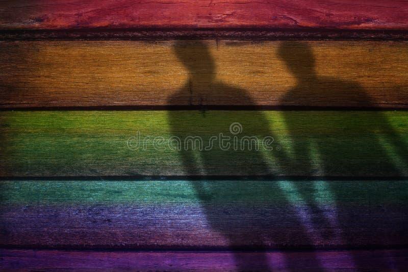 La forma borrosa de la sombra del amante masculino en el arco iris coloreó el tablón de madera imagenes de archivo