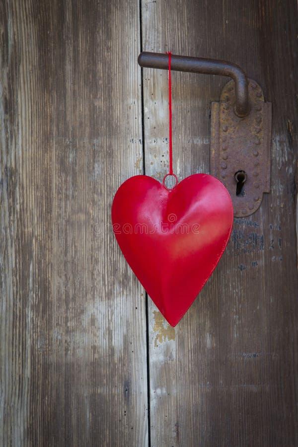 La forma che appende sulla maniglia di porta per il biglietto di S. Valentino, natale del cuore, wed immagine stock libera da diritti