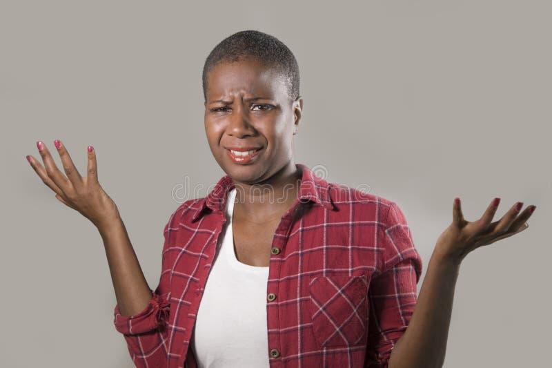 La forma de vida aisló el retrato de la mujer afroamericana negra bonita e infeliz joven que gesticulaba con las manos y la expre foto de archivo