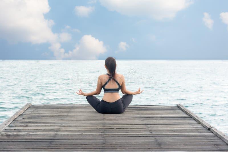 La forma de vida sana de la mujer medita practicar y energía equilibrados de la yoga en el puente foto de archivo