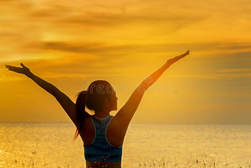 La forma de vida sana de la mujer de la silueta que se relaja y que ejercita vital medita y yoga practicante en la playa en la pu foto de archivo libre de regalías