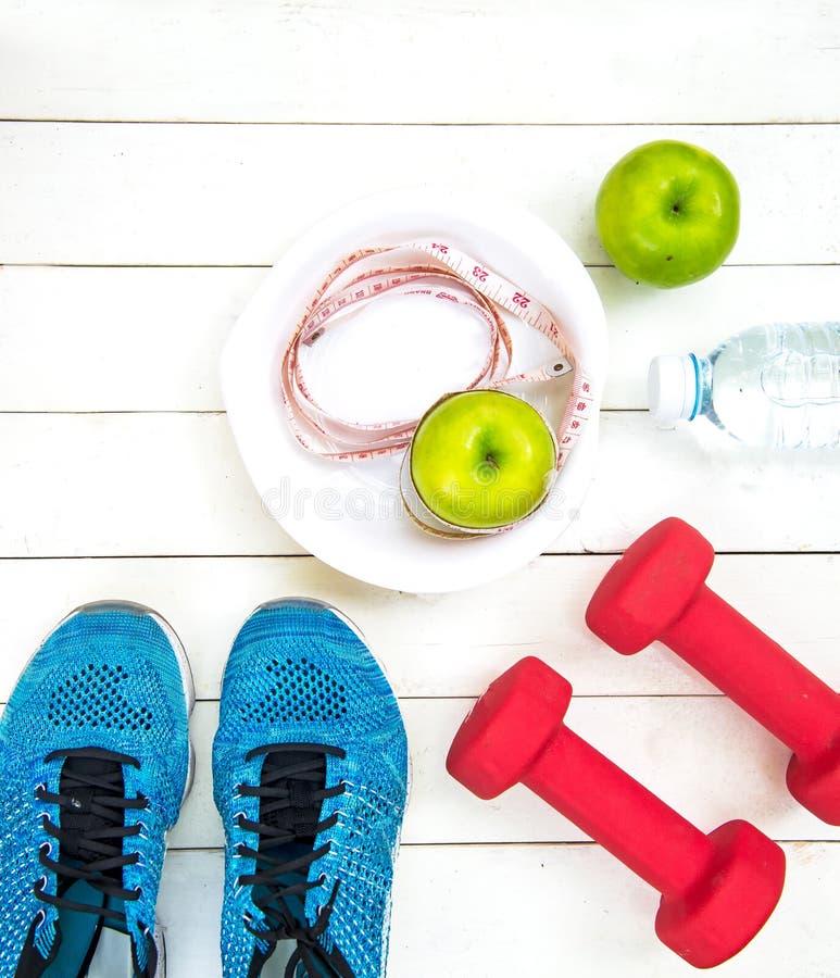 La forma de vida sana para las mujeres adieta con el equipo de deporte, zapatillas de deporte, cinta métrica, da fruto las manzan foto de archivo