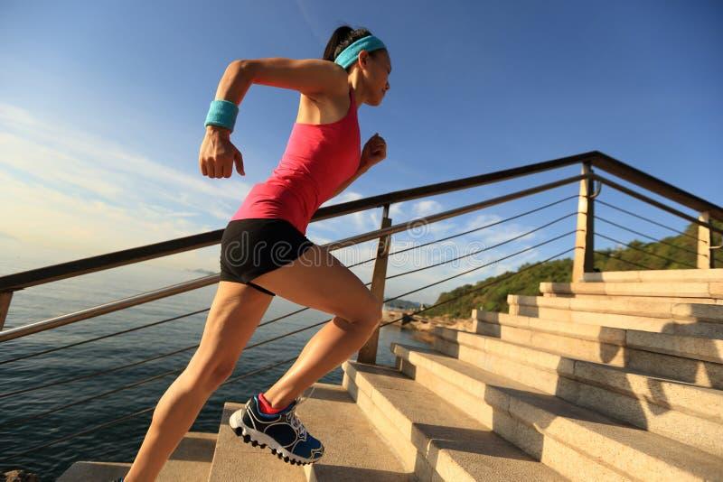 La forma de vida sana se divierte a la mujer que corre para arriba en la salida del sol de piedra de las escaleras imagenes de archivo