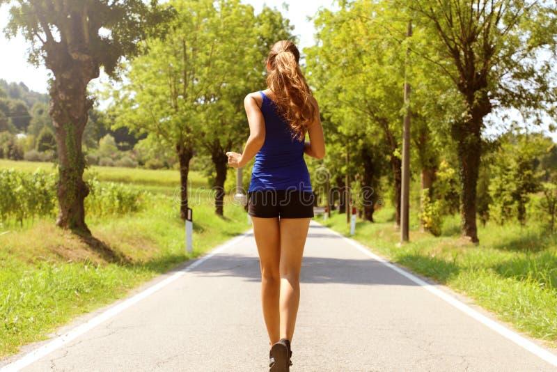 La forma de vida sana se divierte a la mujer que corre en la calzada del asfalto Mujer de la aptitud que corre en la carretera de imagenes de archivo