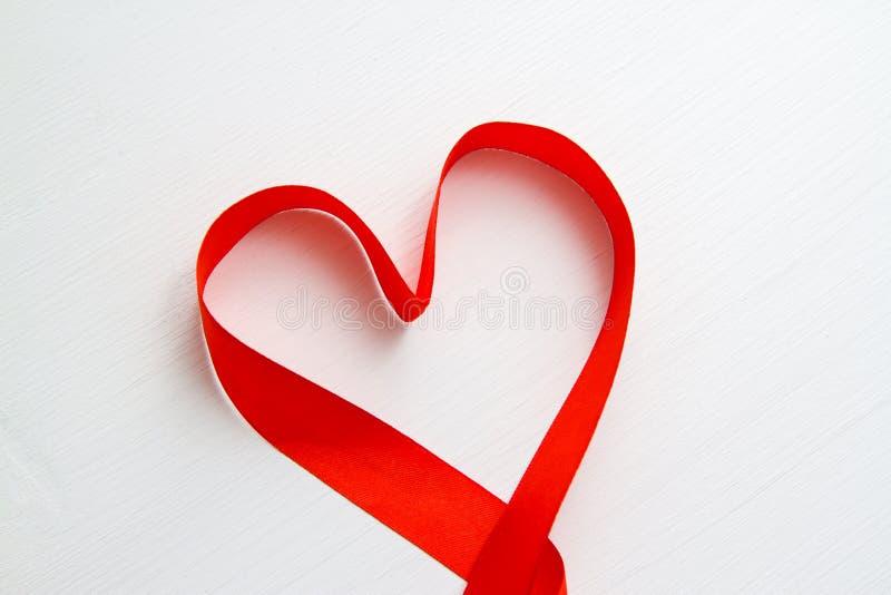 La forma del corazón hizo de cinta roja en el fondo de madera blanco espacio de la copia - concepto del día de las tarjetas del d imágenes de archivo libres de regalías