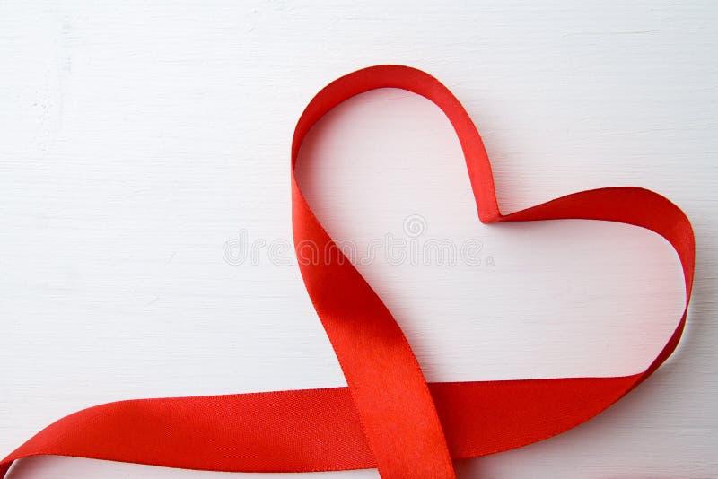 La forma del corazón hizo de cinta roja en el fondo de madera blanco espacio de la copia - concepto del día de las tarjetas del d foto de archivo