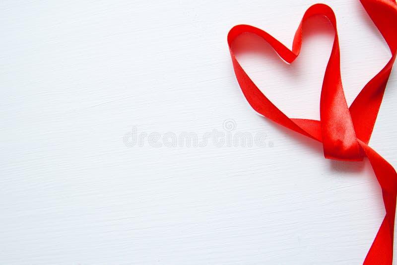 La forma del corazón hizo de cinta roja en el fondo de madera blanco espacio de la copia - tarjetas del día de San Valentín y mad foto de archivo