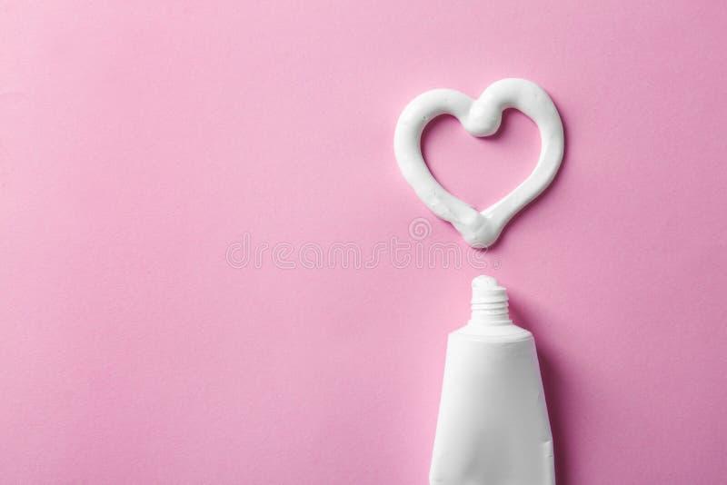 La forma del corazón hizo de la crema dental cerca del tubo y del espacio para el texto en fondo del color foto de archivo