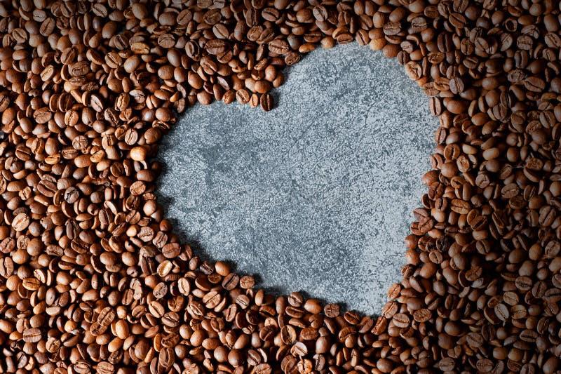 La forma del corazón hizo de fondo asado marrón y negro de los granos o de los granos de café imágenes de archivo libres de regalías