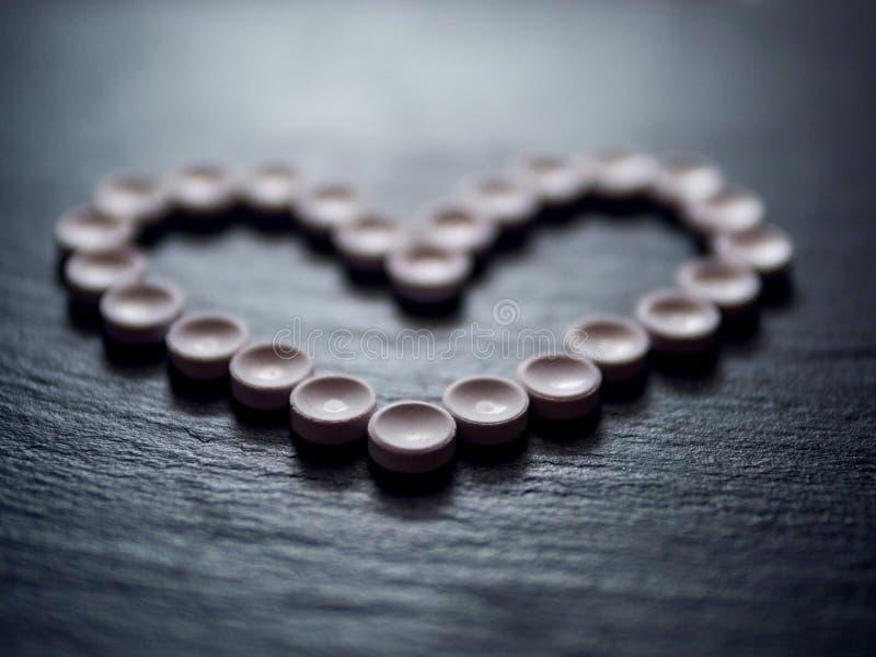 La forma del cuore ha fatto delle pillole, la sanità di concetto, medicina Illuminazione lunatica Fuoco selettivo immagini stock libere da diritti