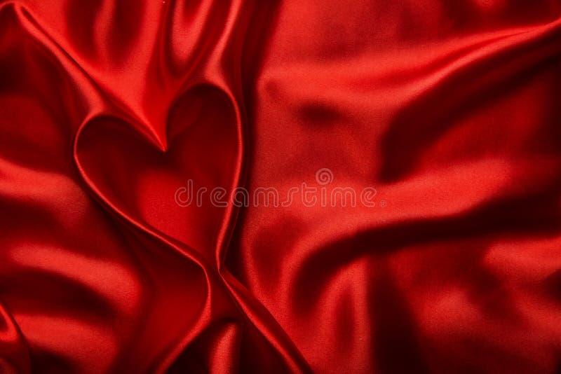 La forma del cuore, il fondo di seta rosso del panno, tessuto piega come estratto fotografia stock libera da diritti