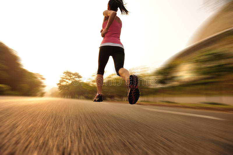 La forma fisica sana di stile di vita mette in mostra le gambe correnti della donna fotografia stock