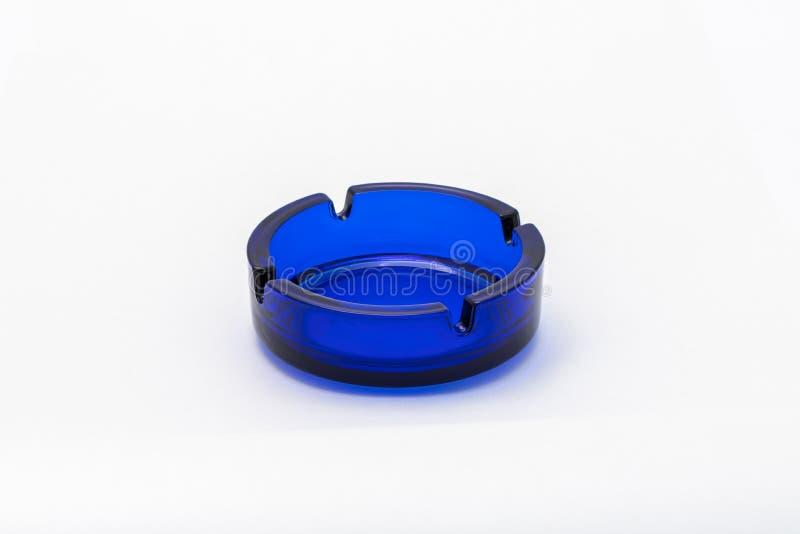 La forma redonda azul vacía del cenicero de cristal se coloca en un fondo blanco foto de archivo