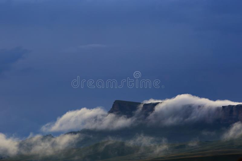 La formación de niebla y de nubes durante puesta del sol sobre las montañas fotografía de archivo libre de regalías
