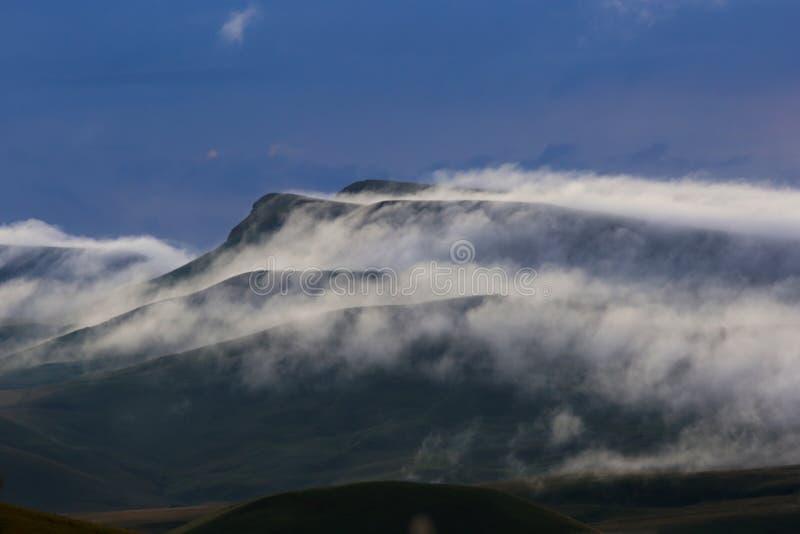 La formación de niebla y de nubes durante puesta del sol sobre las montañas fotografía de archivo
