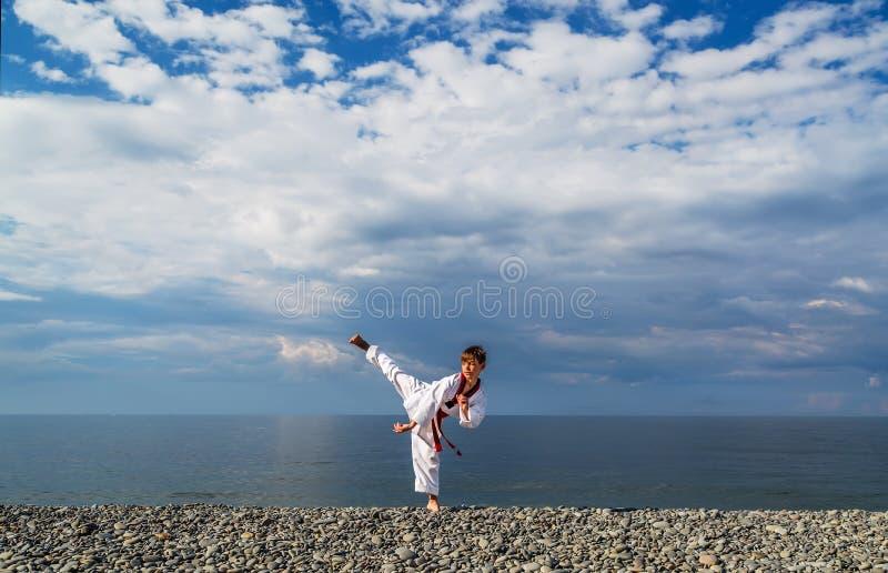 La formation de garçon sur la plage image stock