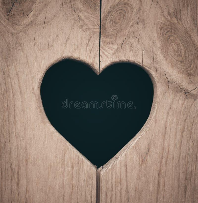La forme de coeur a coupé sur le mur en bois, toilette, porte de carte de travail ou image stock